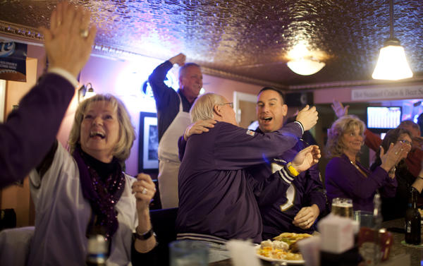 Lynn Street, Jim Andrews, Bill Eder, Chris Leaverton, and Deb Mastracci, all Catonsville residents, cheer over a Ravens touchdown during the Super Bowl at Ship's Cafe.