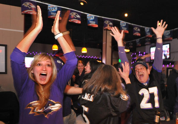 Baltimore, MD - 2/3/13 - Cheering at the bar at Swallow in the Hollow on York Road in Govans are Danielle Judge, Dale Warram (back to camera) and Steve Barrick, all of Baltmore. They were watching the Ravens-49ers Super Bowl at . Amy Davis /Baltimore Sun - #8632