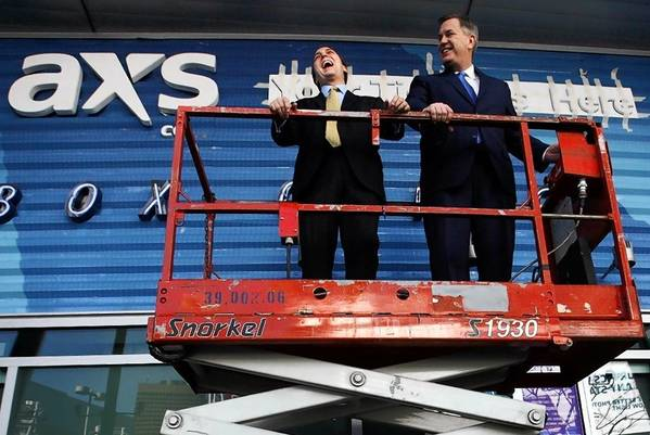 AEG executives Bryan Perez, left, and Tim Leiweke ride a scissors jack outside the ticket office at Staples Center on Feb. 1, 2013, as workers were putting the finishing touches on its new look.