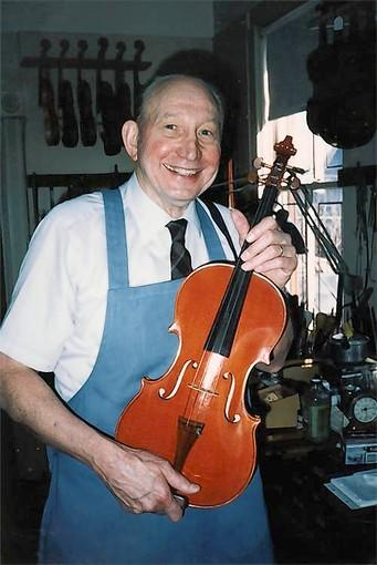 At 92, Carl F. Becker holds one of the last violins he made, his son said. He died at 93.