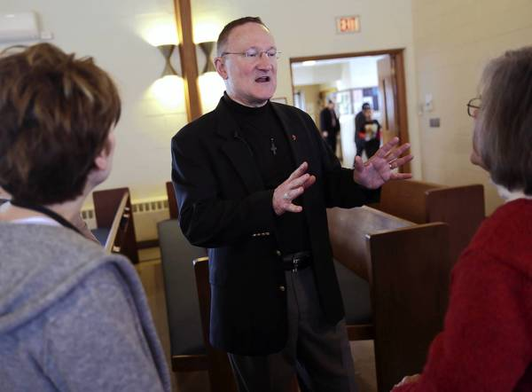 The Rev. Rex Piercy greets members of Congregational United Church of Christ of Arlington Heights after a service Sunday. Church leaders passed out fliers encouraging congregants to contact the Boy Scouts of America to express opposition to its ban on gay Scouting members and leaders.