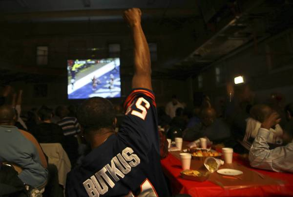 Wearing a Dick Butkus jersey, Darrell Hicks cheers a Baltimore Ravens touchdown during a sober Super Bowl party Sunday at the Salvation Army's Harbor Light Center on Chicago's Near West Side.