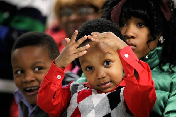 Isaiah McKay, 3, signs as Mataeau Perry, 13, holds him during a worship service last month to mark the eighth anniversary of the Praetorium Sign Language Church in Chicago.