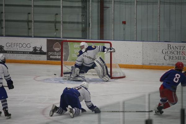 Cougars¿ goalie Nick Dalchow makes a save against the shot of Cory Roach (8) of Brookings Sunday in Aberdeen. American News Photo by John Papendick