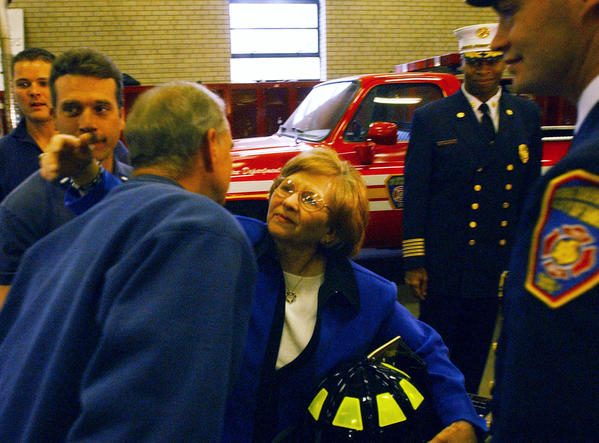 Marian Schumaker hugs Raymond Kasey, a captain at the Hartford Fire Department's Engine Company 11, after she was honored by the department for her bravery in assisting patients at the Greenwood Health Center where she was a nursing supervisor during the tragic fire that occurred there on February 26, 2003. Schumaker was presented with an honorary fire department member plaque at Engine Company 11, the first to respond to the fire.