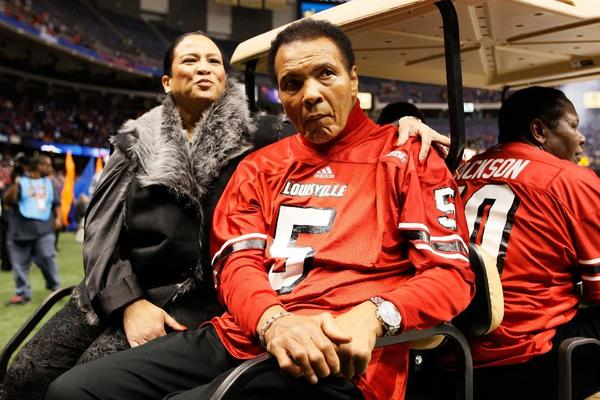 Muhammad Ali rides a golf cart onto the field for the coin toss before the start of the Sugar Bowl.