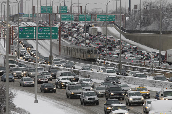 Traffic on the inbound and outbound lanes of the Kennedy Expressway, seen from Addison Street, moves slowly on a snowy morning in Chicago.
