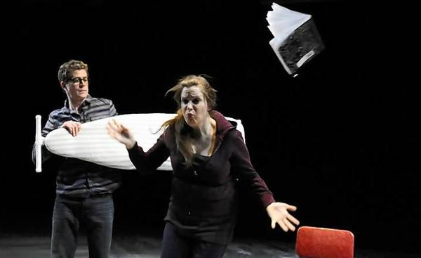 "Jess Watkins is struck by an ironing board swung by Lucas Hall, left, in a scene from TheaterWorks' ""Almost, Maine"" by John Cariani."