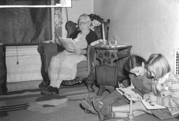 Scheduled blackouts were not unusual in the U.S. during World War II, as Americans prepared for feared enemy attacks. In this picture from 1939, a Baltimore woman and her two young charges occupy themselves by candlelight.