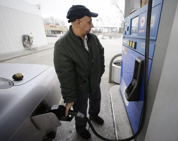 Samir Shabo fills up his tank at a Mobil gas station in Chicago. In 2012, the percentage of household income that Americans spent on gasoline hit a 30-year high, the Energy Department says.