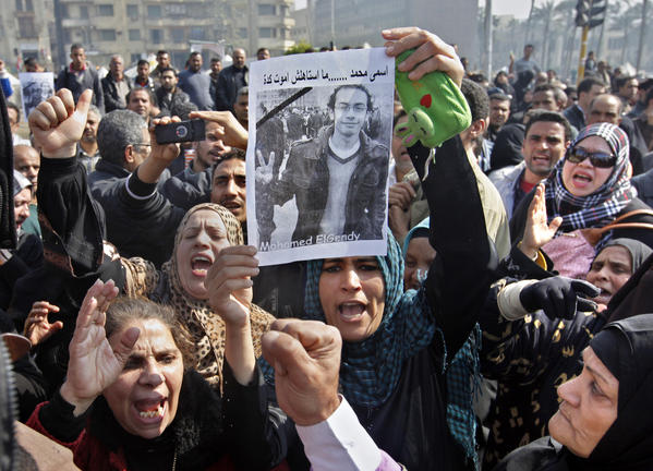 Relatives of Mohamed ElGindy, a 28-year-old Egyptian activist who died of injuries sustained during or after a protest last week, hold up his picture as they shout slogans against President Mohamed Morsi during a funeral procession in Cairo's Tahrir Square.