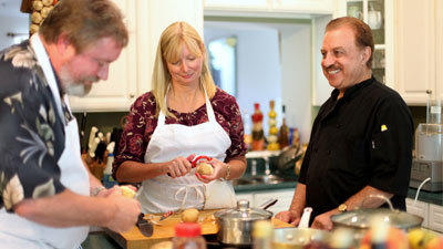 David and Michelle Byrnes peel potatoes to make garlic mashed potatoes during a cooking lesson with chef Ben Tehranian.