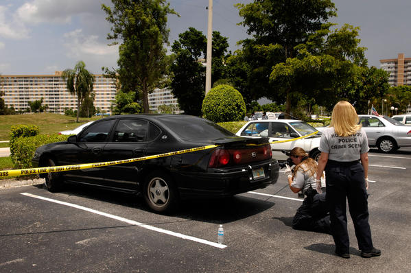 Police gather evidence in a parking lot on the 4300 block of Hillcrest Drive where a suspect attempted to carjack a motorists after allegedly shooting an BSO officer Maury Hernandez during a stop. The alleged shooter, David Maldonado, 23, shot an off-duty Broward County sheriff's detective Deputy Maury Hernandez, 28. during a routine traffic stop on the 3700 block of Pembroke Road in Pembroke Park.