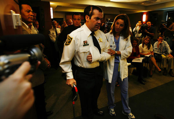 "Deputy Maury Hernandez, who was shot in the head two months ago, walks with the help of his physical therapist  Sandra Lettier.   Hernandez has made a ""miraculous""  recovery , according to doctors at  Hollywood Memorial hospital, in Hollywood , Florida. .   He was  joined  his family and doctors during a press conference."