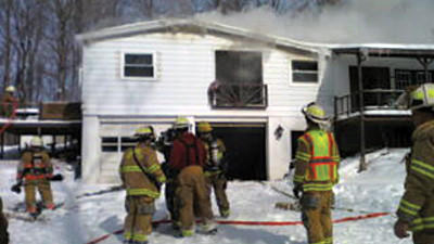 This cell phone photo shows volunteer firefighters battling a house fire Monday along Keyerstown Road in Lincoln Township