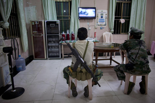 Kachin Independence Army soldiers watch TV at a restaurant in Laiza, Myanmar.