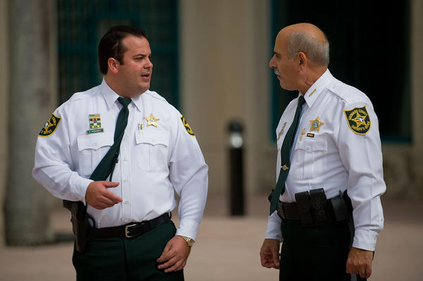 Maury Hernandez, a Broward sheriff's deputy who rejected disability retirement after he was shot in the head in the line of duty, speaks with sheriff Al Lamberti  before a press conference at the Public safety Building in Fort Lauderdale. Hernandez was promoted to sergeant Friday, ending a long dispute with the Broward Sheriff's Office.