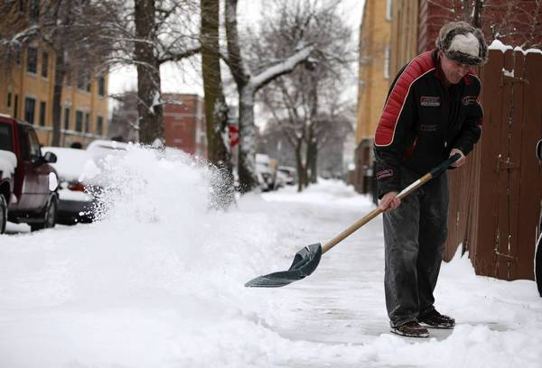 Lazar Cornel shovels the snow from the sidewalk near his home in the Logan Square neighborhood in Chicago.