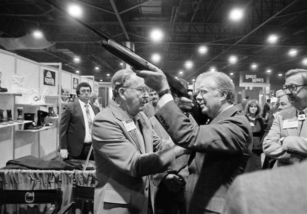 President Carter sights down the barrel of a shotgun as Reinhart Fajen, a gunstock manufacturer, checks the fit, in Atlanta as Carter stopped during a visit to the national shooting sports foundation shot show at the World Congress Center in 1984.
