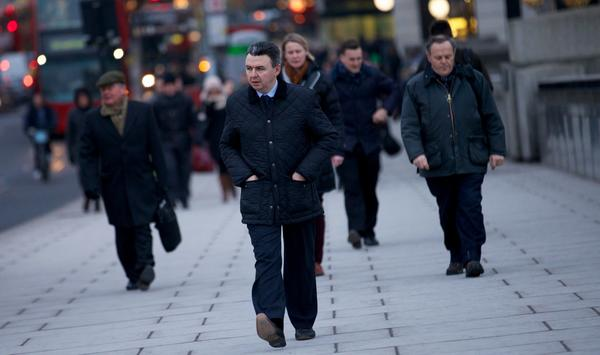 Commuters walk across London Bridge in the City of London on January 25, 2013.