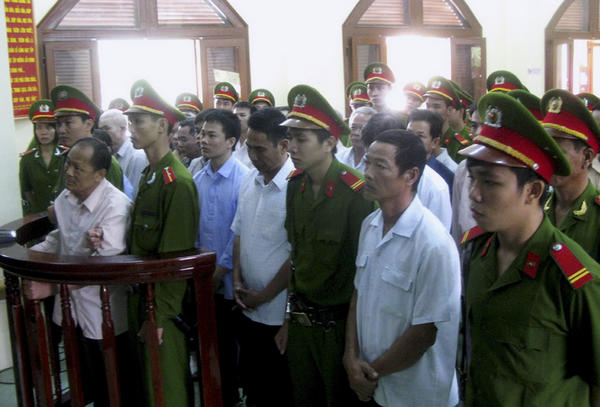 Phan Van Thu, second from left, stands with members of his organization, flanked by policemen, as the verdict is read in the People's Court of Phu Yen province.