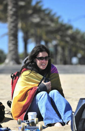 A young woman wraps up to stay warm on Fort Lauderdale's beach. Temperatures should warm quickly by this afternoon.