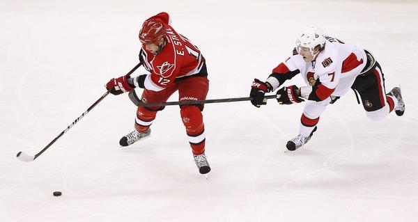The Ottawa Senators' Kyle Turris (R) battles the Carolina Hurricanes' Eric Staal for the puck during the first period of their NHL hockey game in Raleigh, North Carolina February 1, 2013.