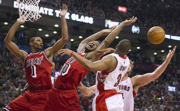 Toronto Raptors players and Miami Heat players scramble for a rebound in the first half of their NBA basketball game in Toronto February 3, 2013.