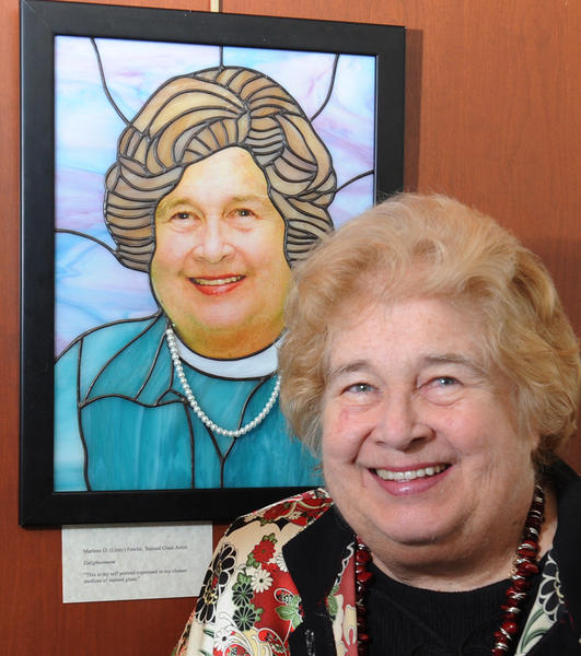 "In photo, Marlene O. (Linny) Fowler, stands next to her stained glass art called ""Enlightenment.""  15 artists and 15 non artists from Bethlehem, including Mayor Callahan, Neville Gardner and Jeff Parks, contributed self-portraits for a show at the Rotunda Gallery at Bethlehem City Hall."