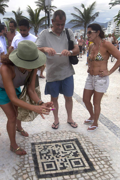 Beachgoers scan the newly installed QR code at Arpoador rock.