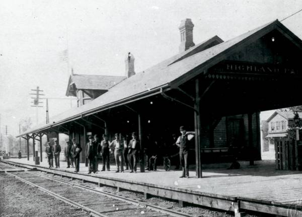 Commuters wait for the train to Chicago at the Highland Park Train Depot, ca. 1896-1910. Evidence suggests it was taken by Orson B. Brand and donated to the Historical Society by Leslie Brand or Salome Brand Roeber. Printed copies of the image variously identify the man in the foreground as John C. or Frank Duffy, descendants of early Highland Park settlers and active participants in the development of the town and its government.