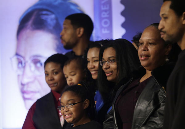 Family members of Rosa Parks stand next to an image of the commemorative postage stamp unveiled on what would have been her 100th birthday.