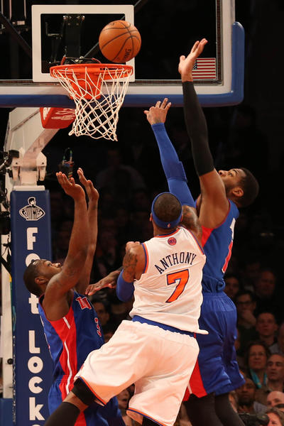 New York Knicks small forward Carmelo Anthony (7) shoots between Detroit Pistons center Andre Drummond, right, and point guard Rodney Stuckey during the first quarter at Madison Square Garden.