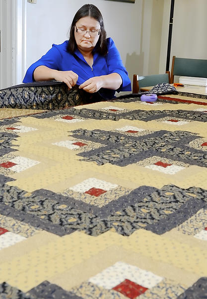 Susan Stull works on a quilt that will be donated to the Potter's Bowl auction to benefit the Community Free Clinic.