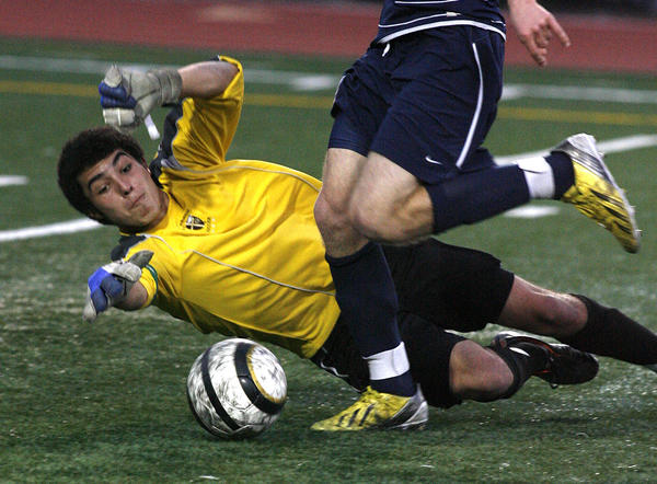St. Francis' Luca Coppola drops and reaches for the ball as Notre Dame's Kyle Ause successfully gets the ball around him to score in the first half in a Mission League soccer match at St. Francis High School in La Canada Flintridge on Monday, February 4, 2013. Notre Dame won the game 4-0.