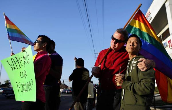 Minh Tran, left, holds a sign and gay pride flag and Bob Tucker hugs his partner, Quan Nguyen, as they join a protest against the exclusion of a gay rights organization from Westminister's Tet parade.