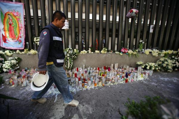 A man passes candles and flowers placed in front of the Pemex central building in Mexico City.