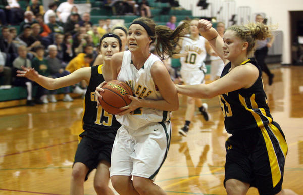 Aberdeen Roncalli's Mollee Karst, center, goes up for a shot as Groton's Halle Dohman, left, and Carly Wheeting, right, play defense on Monday at Roncalli Gym.
