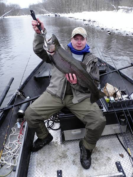 Josh Day, formerly of Orefield and now a professional fishing guide on the Salmon River out of Pulaski, N.Y., displays a steelhead caught on his drift boat.