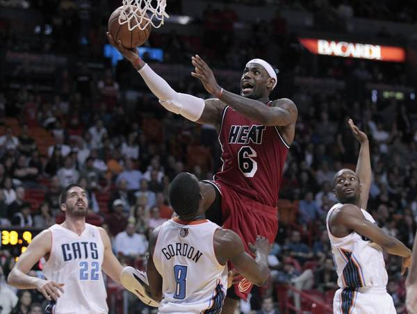 Miami Heat's LeBron James drives against Charlotte Bobcats' Byron Mullens (L), Ben Gordon (C) and Kemba Walker in the second half of their NBA basketball game in Miami, Florida February 4, 2013.