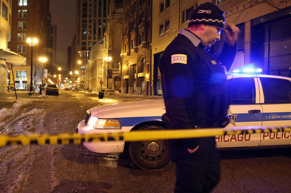 A police officer guards the 800 block of North Rush Street in Chicago after a man was shot outside an apartment building on the west side of the block at about 5:30 a.m. today.