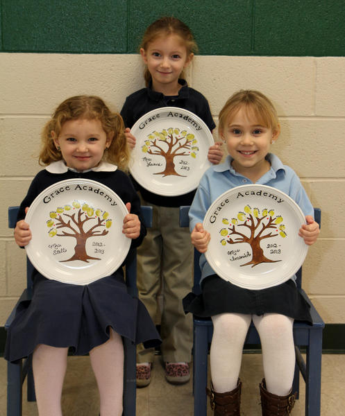These Grace Academy students are holding their personalized plates from their class. Seated, from left, Elizabeth Young (K3) and Piper Meredith (K4), and standing, Makenna Jordan (K5).