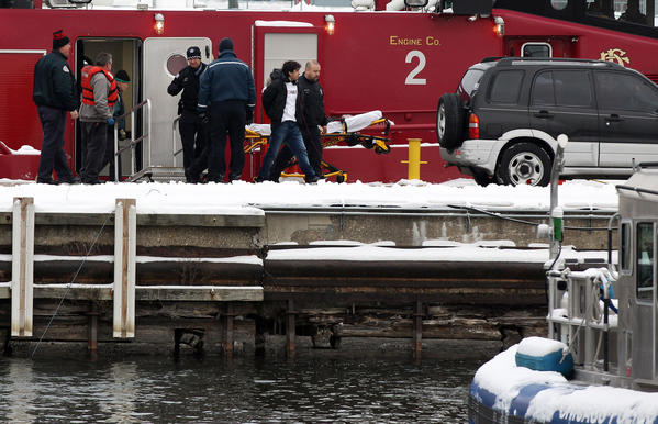 A police officer escorts a man from a fire boat docked on the Chicago Marine Safety Station at DuSable Harbor today. The man was rescued earlier from the breakwater near Monroe Harbor.