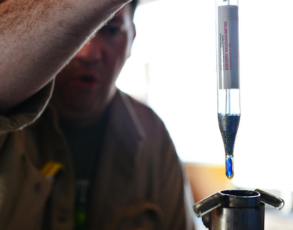 Michael Sexton's takes a measurement of his beer during the larger scale brewing process. Homebrewer Michael Sexton's Black Rye Pale Ale was chosen as Lehigh Valley Beer Week's official beer. Bethlehem Brew Works is helping him brew his beer on a much larger scale.