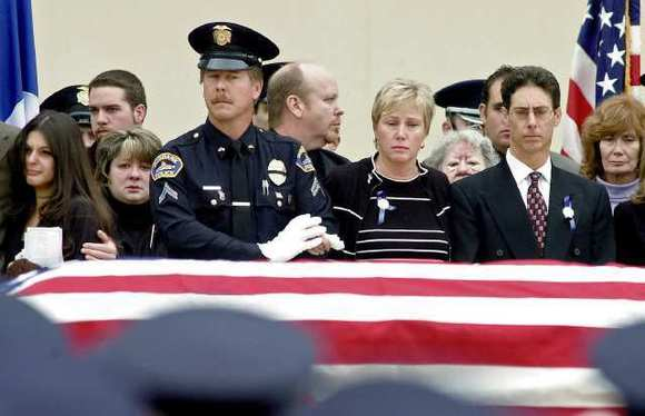 From the left, girlfriend Jessica diCristins, Burbank Police Sgt. Darin Ryburn, and parents Sue and Mike Pavelka stand as the casket is presented at Officer Matthew Pavelka's funeral on November 21, 2003.