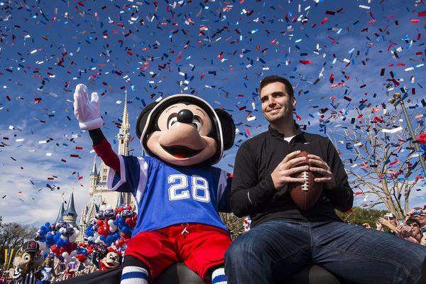 Super Bowl MVP Joe Flacco celebrates with Mickey Mouse during a parade at Disney World in Orlando.