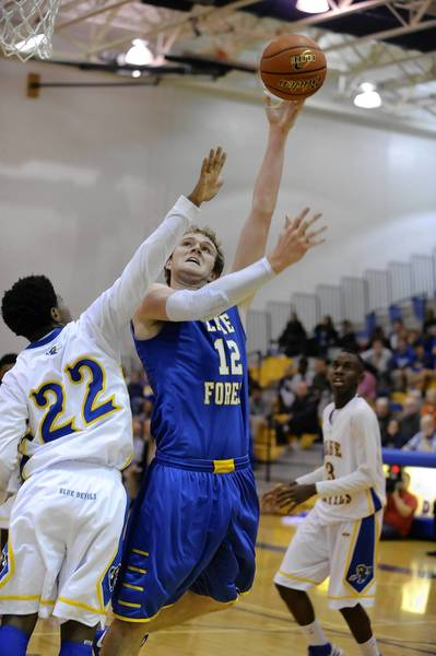 Lake Forest's Evan Boudreaux shoots a hook shot over Warren's Derek Mason. Lake Forest defeated Warren 36-28 on Dec. 14.