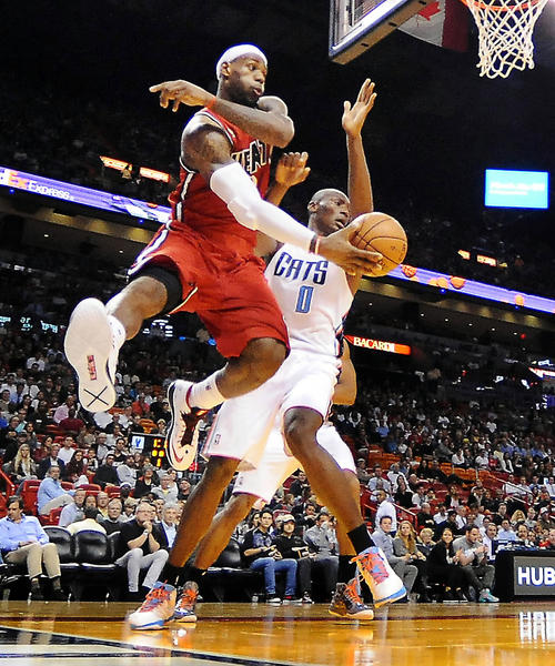 Miami's LeBron James passes the ball from under the basket while defended by Bismack Biyombo.