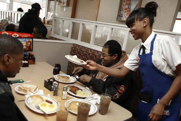 Gail Robertson serves pancakes at IHOP to regular customers and brothers Donald, left, and Brian Thompson.