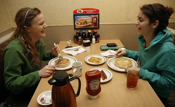 Anna Wahlstrom, left, and Sarah Becouvarakis enjoy their pancakes at IHOP to support charity -- and because they really love pancakes.